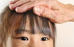 Children eye closeup selective focus with her grandmother care. Stock Photos
