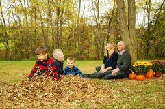 Children in Fall leaves with parents Stock Photo