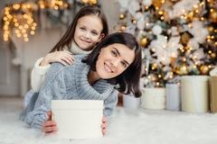 Children, family and celebration concept. Adorable female in knitted sweater holds white present box and small kid stands behind. Her back, have good mood royalty free stock images