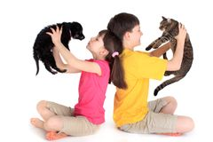 Children with family pets. Brother and sister sit back to back holding their family pets, a tabby cat and a puppy dog Royalty Free Stock Image