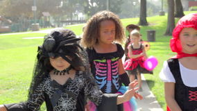 Children In Fancy Costume Dress Going Trick Or Treating. Camera follows group of children as they walk through park wearing trick or treat fancy dress costumes stock video footage