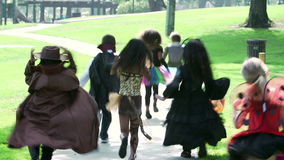 Children In Fancy Costume Dress Going Trick Or Treating. Group of young children dressed in costumes to go trick or treating running away from camera.Shot on stock footage