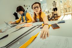 Children of fashion designer helping their mother drawing sketches. Children of designer. Children of famous fashion designer helping their mother drawing royalty free stock image