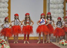 Children fashion models in red coifs and skirts Royalty Free Stock Photography
