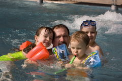 Children with father. Happy children in swimming-pool royalty free stock photos