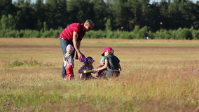 Children with the father spend time together in the field stock video footage