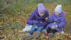 Children feed each other marmalade and cocoa. slow-motion. Two sisters drink cocoa with marshmallows in the autumn park stock video