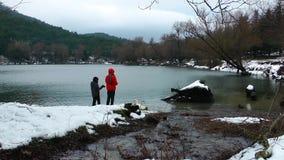 Children Feeding the Goose near the Lake in Winter stock video