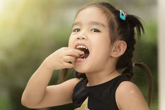 Children feel happy eating candy. In the garden royalty free stock image