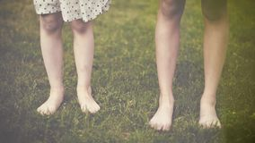 Children feet on green grass
