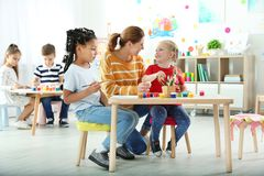 Children with female teacher at painting lesson. Indoors stock image