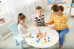 Children with female teacher at painting lesson. Indoors stock photography