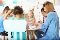 Children with female teacher at painting lesson. Indoors stock photo