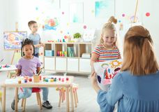 Children with female teacher at painting lesson. Indoors royalty free stock image