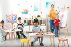 Children with female teacher at painting lesson. Indoors royalty free stock images