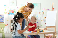 Children with female teacher at painting lesson. Indoors royalty free stock photo