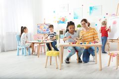 Children with female teacher at painting lesson stock photo