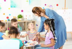 Children with female teacher at painting lesson. Indoors stock images