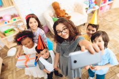 Children in festive attire and holiday hats make selfie, together at birthday party. Together photo at birthday party Stock Image