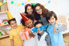 Children in festive attire and holiday hats make selfie, together at birthday party. Together photo at birthday party Stock Images