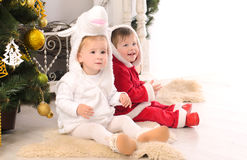 Children in festive attires at christmas tree Royalty Free Stock Image