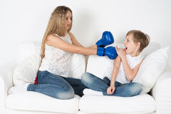Children fight. Girl with boxing gloves hit the boy Stock Photos