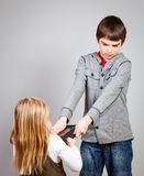 Children fight for tablet computer Stock Image