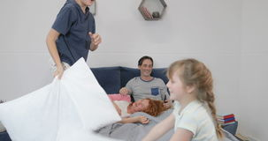 Children fighting with fight on parents bed, happy family fun in morning at home stock video