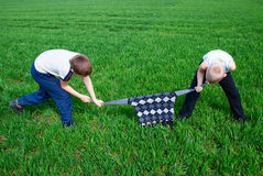 Children fighting over a sweater. On a green field Stock Images