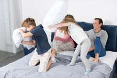 Children Fighting Pillows, Family Having Fun Bedroom, Parents With Daughter And Son Cheerful Together Stock Photo