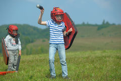 Children fighting with shield Royalty Free Stock Image