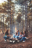 Children by the fire in autumn forest. Group of kids with mom sitting by the fire and drinking tea in autumn forest, hike at weekend stock photography