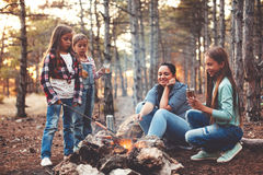 Children by the fire in autumn forest Stock Photos