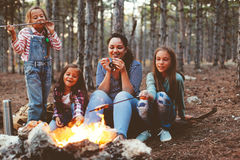 Children by the fire in autumn forest. Group of kids with mom sitting by the fire and drinking tea in autumn forest, hike at weekend stock photo