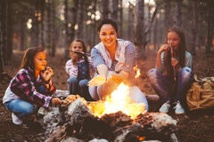 Children by the fire in autumn forest. Group of kids with mom sitting by the fire and drinking tea in autumn forest, hike at weekend royalty free stock photo