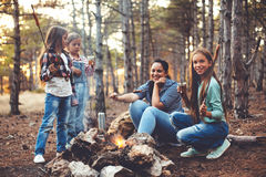 Children by the fire in autumn forest. Group of kids with mom sitting by the fire and drinking tea in autumn forest, hike at weekend royalty free stock photography