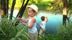 Children fish on the bank of a pond. Children fish on the bank of a pond. stock footage