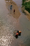 Children Fishermen. A group of poor Children collecting fish with small net in a river in India Stock Photo