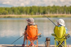 Children with fishing rods sit on a wooden pier and fish. At the lake Stock Image