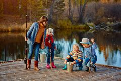Children fishing watching the catch of a friend. Wooden pier, the  autumn Sunny weather Royalty Free Stock Images