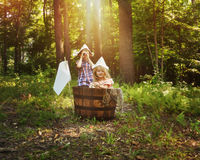 Children Fishing in Wooden Boat in Forest. A little boy and girl are pretending to fish in a wooden barrel boat in the nature woods with a real fish being caught stock images