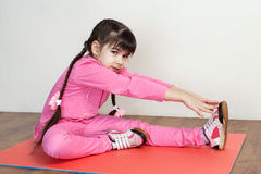 Children. Fitness. Flexibility. Children. Fitness. A cute little girl in a pink sport suit performing stretching to the foot stock photography
