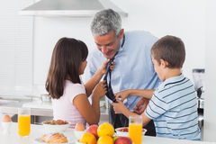 Children fixing their fathers tie in the kitchen Royalty Free Stock Images