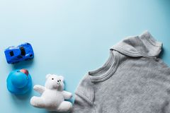 Children flat lay with clothes blue background top view space for text . baby blue car , duck , teddy, clothing.  royalty free stock photo