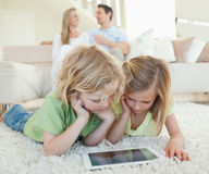 Children on the floor with tablet and parents behind them Royalty Free Stock Images