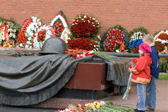 Children with flowers and eternal flame. The celebration of Victory day in Russia Stock Photography