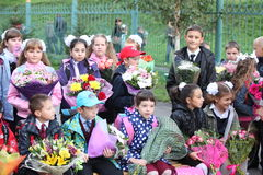 Children with flowers in front of the School No. Royalty Free Stock Photography