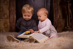 Children on a fluffy carpet with book Stock Photo