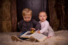 Children on a fluffy carpet with book Royalty Free Stock Image