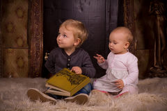 Children on a fluffy carpet with book Stock Image
